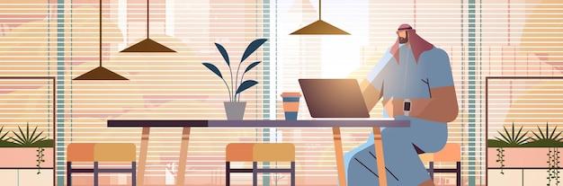 Arabische zakenman zittend op de werkplek arabische zakenman freelancer werken in creatieve kantoor horizontale portret vectorillustratie