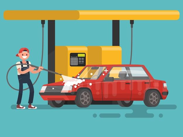 Arbeider die een auto wast bij de autowasserette.