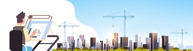 Architect blauwdruk puttend uit verstelbare bord over bouwplaats