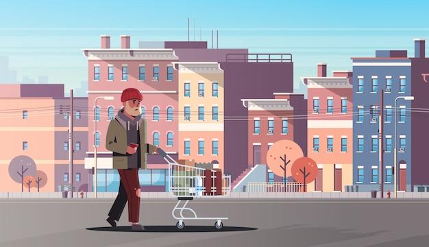 Arme man duwen trolley kar met bezittingen bedelaar man lopen straat bedelen voor hulp daklozen moderne stadsgebouwen stadsgezicht