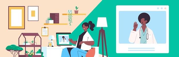 Arts op laptop scherm raadplegen afro-amerikaanse vrouwelijke patiënt online overleg gezondheidszorg geneeskunde medisch advies concept woonkamer interieur horizontaal portret