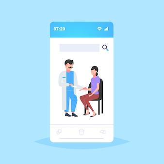 Arts spuit houden injectie vaccin vaccin gegeven aan vrouw patiënt vaccinatie gezondheidszorg geneeskunde concept smartphone scherm mobiele applicatie volledige lengte