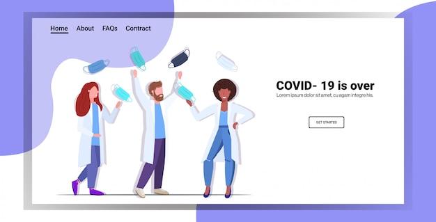Artsenteam dat gezichtsmaskers opstijgt ter ere van de overwinning op de pandemie van het coronavirus quarantaine covid-19