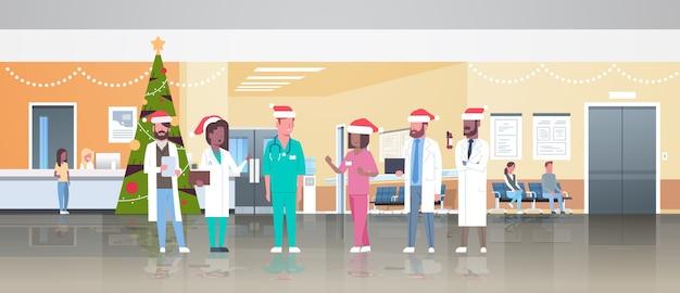 Artsenteam in santa hoeden staan samen geneeskunde gezondheidszorg concept kerstmis nieuwjaar vakantie viering moderne ziekenhuis gang interieur