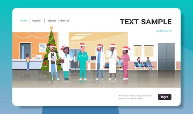 Artsenteam in santahoeden staan samen geneeskunde gezondheidszorg concept kerstmis nieuwjaar vakantie viering moderne ziekenhuis gang bestemmingspagina