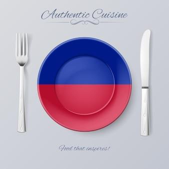 Authentieke keuken van haïti plaat met haïtiaanse vlag en bestek