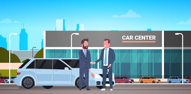 Auto showroom, aankoop verkoop of rental center verkoper man geeft sleutels aan eigenaar