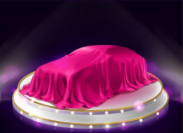 Autopresentatie, auto bedekt met sluier op het podium