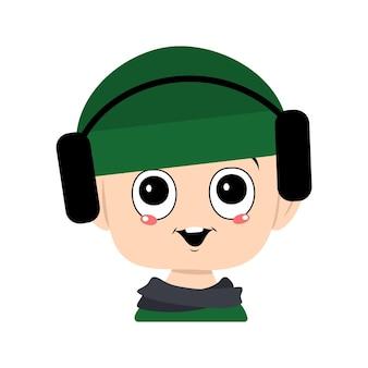 Avatar van een kind met grote ogen en een brede glimlach in een groene hoed met koptelefoon. een schattig kind met een vrolijk gezicht in een herfst- of winterhoofdtooi en sjaal. hoofd van schattige baby met blije emoties