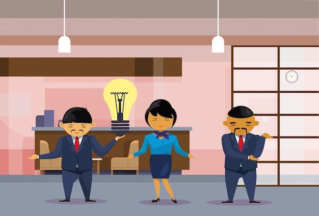 Aziatisch bedrijfsmensenteam die gloeilamp houden