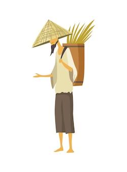 Aziatische boer in stro conische hoed. azië plattelandscultuur. chinese boer draagt opbrengst rijstoogst