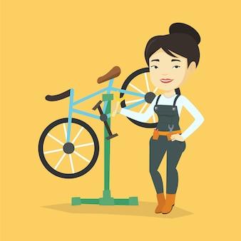 Aziatische fietswerktuigkundige die in reparatiewerkplaats werkt.