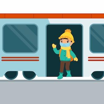 Aziatische schooljongen stapt uit de trein en zwaait met zijn hand. leuke ondergeschikte middelbare schoolstudent met een medisch masker op zijn gezicht.