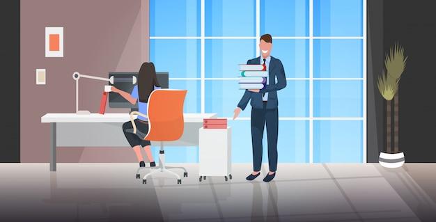 Baas documenten stapel geven aan overwerkte vrouwelijke werknemer