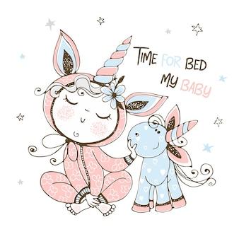 Baby in pyjama met zijn eenhoornstuk speelgoed. het is tijd om te gaan slapen.
