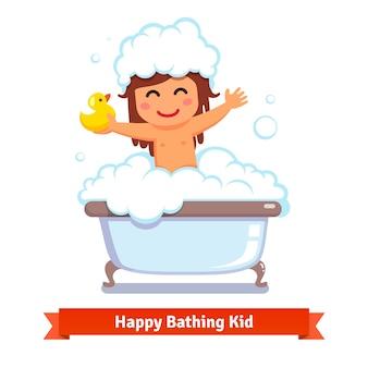 Baby meisje met bad met eend speelgoed en bubbels