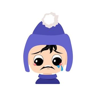 Baby met huilen en tranen emotie verdrietig gezicht depressieve ogen in blauwe hoed met pompon jongen met melanch...