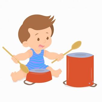 Babyjongen met behulp van houten lepels om pannen te knallen