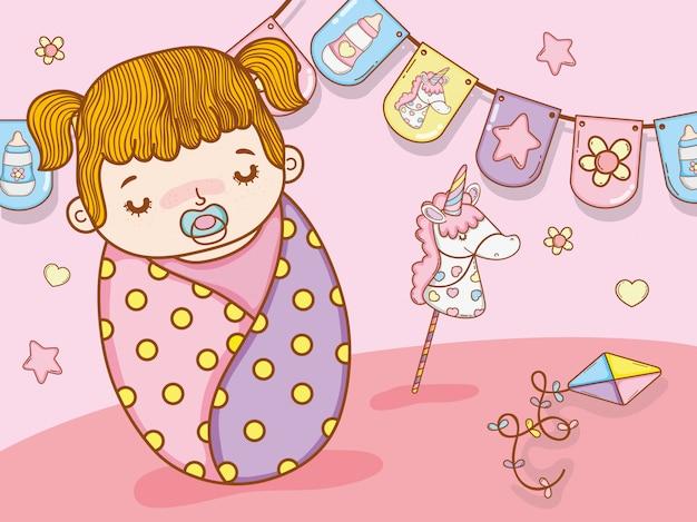 Babymeisje met partijvlaggen en eenhoornstuk speelgoed