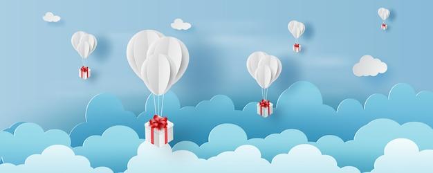 Ballonwit drijvend en geschenkdoos in de lucht