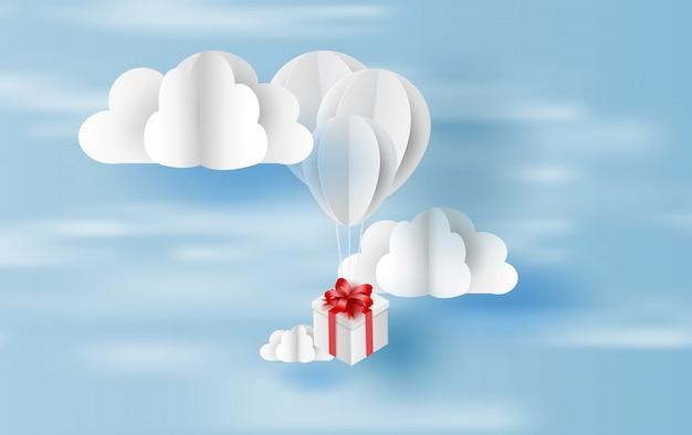 Ballonwit drijvend en geschenkdoos