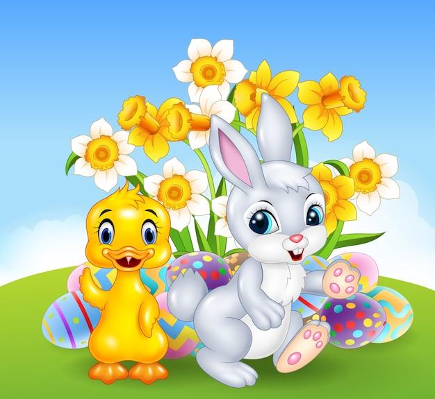 Beeldverhaal gelukkig eend en konijntje met kleurrijke paaseieren