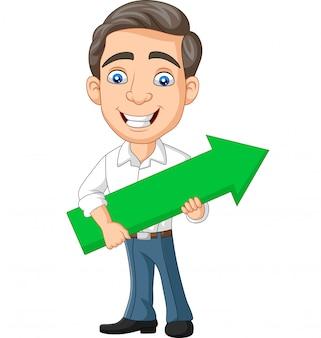 Beeldverhaal jonge zakenman die een groene pijl houdt