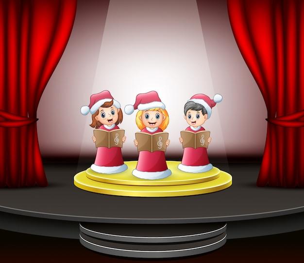 Beeldverhaalkinderen die kerstmishymnes op het stadium zingen