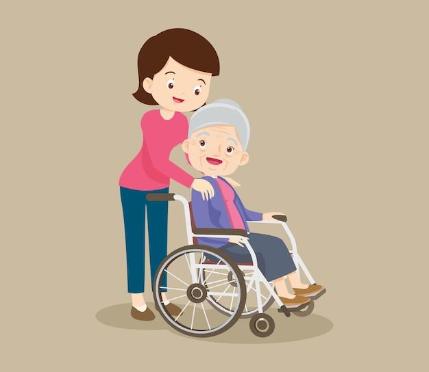 Bejaarde vrouw zit in een rolstoel en haar dochter legt teder de handen op haar schouders