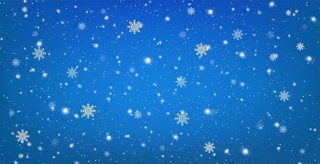 Besneeuwde blauwe achtergrond met vallende sneeuwvlokken. kerst winter sneeuwval met witte sneeuwvlokken.