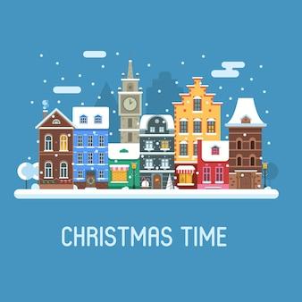 Besneeuwde kerststad straat vlak landschap met kleurrijke europese huizen en nieuwjaarsversieringen