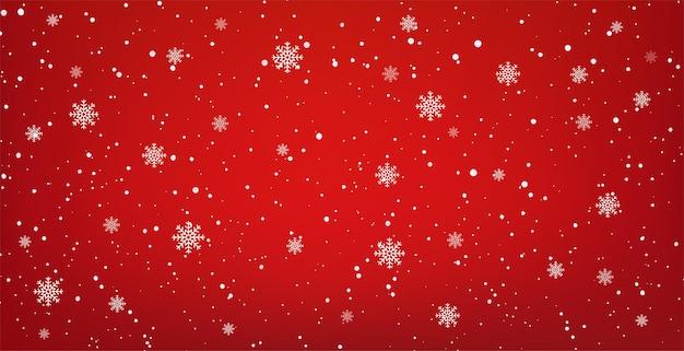 Besneeuwde rode achtergrond met vallende sneeuwvlokken. kerst winter sneeuwval met witte sneeuwvlokken.