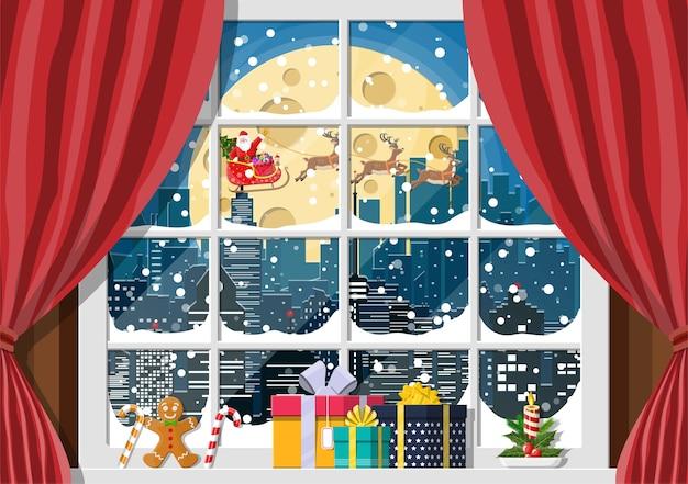 Besneeuwde stadsgezicht met santa op venster