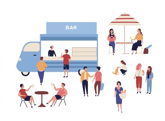 Bestelwagen en grappige mensen die ernaast lopen, aan tafels zitten, koffie drinken en met elkaar praten.