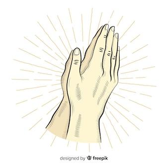 Biddende handen met stralenachtergrond