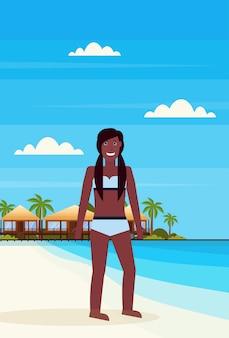 Bikini vrouw op tropisch eiland met villa bungalow hotel op strand aan zee groene palmen landschap zomervakantie plat