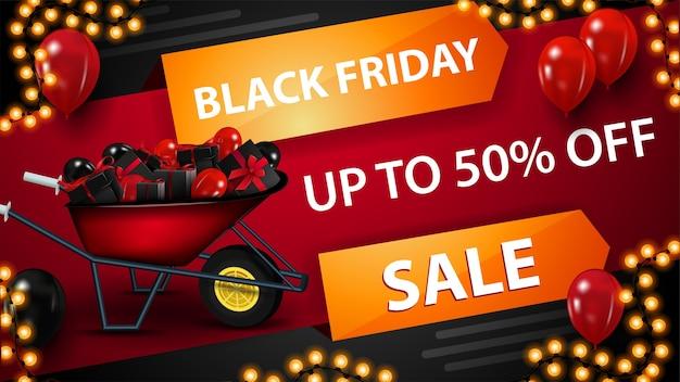 Black friday rode kortingsbanner met kruiwagen met cadeautjes voor zwarte vrijdag, ballonnen in de lucht en slingerframe