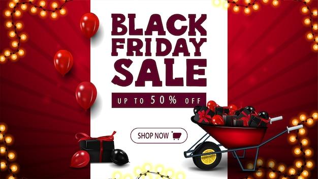 Black friday-uitverkoop, rode kortingsbanner met witte grote streep in het midden met aanbieding, kruiwagen met cadeautjes voor zwarte vrijdag, slingerframe-ballonnen in de lucht