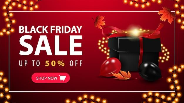 Black friday-uitverkoop, rode kortingsbanner met zwarte geschenkdoos omwikkeld met slinger, vallende esdoornbladeren, ballonnen en slingerframe.