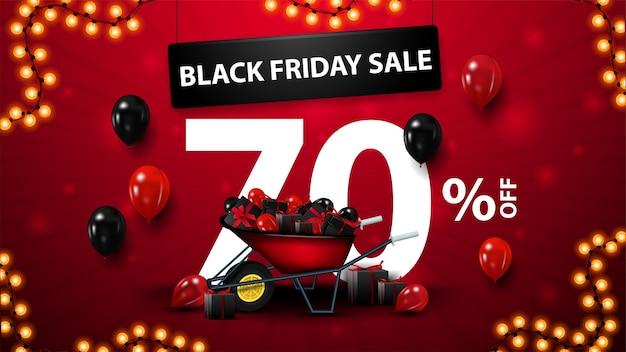 Black friday-uitverkoop, tot 70% korting, rode vlag met groot volumetrisch aanbod, kruiwagen met cadeautjes voor black friday, ballonnen in de lucht en slingerframe