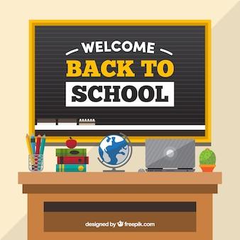 Blackboard en bureau met laptop en materialen