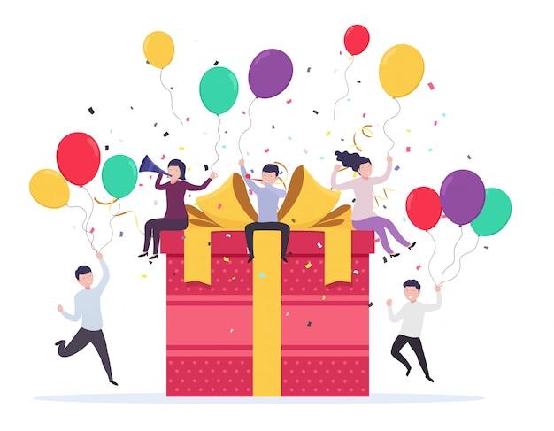 Blije mensen die opduiken in de buurt van een geschenkdoos met ballonnen, confetti, fluitjes en feesttrompetten. verjaardag viering concept, bedrijfsevenement.