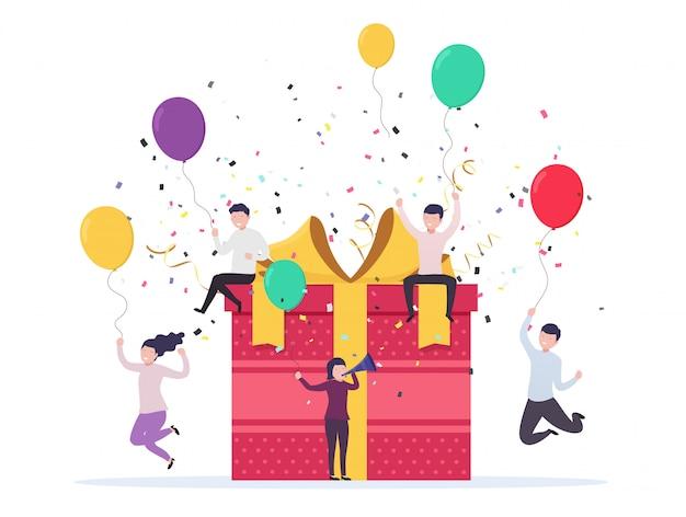 Blije mensen springen uit de buurt van een geschenkdoos met ballonnen, confetti. verjaardag viering concept, bedrijfsevenement.