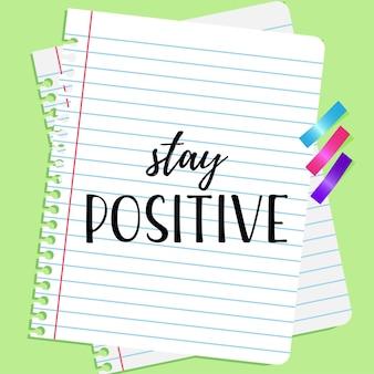 Blijf positief belettering met schoolbriefpapier vlakke afbeelding