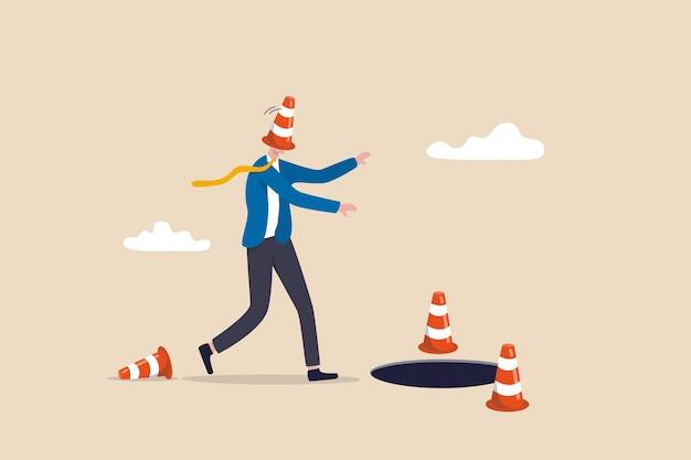 Blinde en gefrustreerde zakelijke richting, fout of mislukking, val of crisis vooruit, risico- en onzekerheidsconcept, blinddoek zakenmandekking met pyloon die loopt om in het gat of de zakelijke val te vallen.