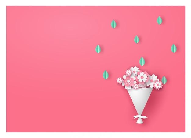 Bloem of boeket in pastel kleurtoon met groene bladeren op roze achtergrond.