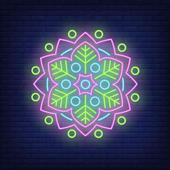 Bloemen rond het neonteken van het mandalapatroon