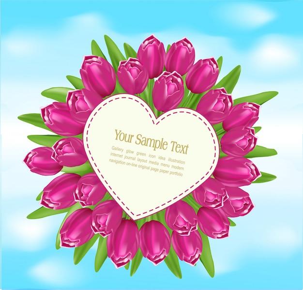 Boeket tulpen met een wenskaart in de vorm van een hart op blauwe hemel