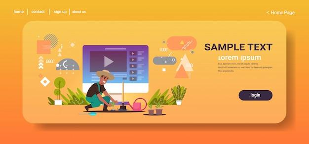 Boer blogger opname online video man vlogger in uniform planten jonge zaailingen in moestuin landbouw zaailing bloggen concept volledige lengte horizontale kopie ruimte