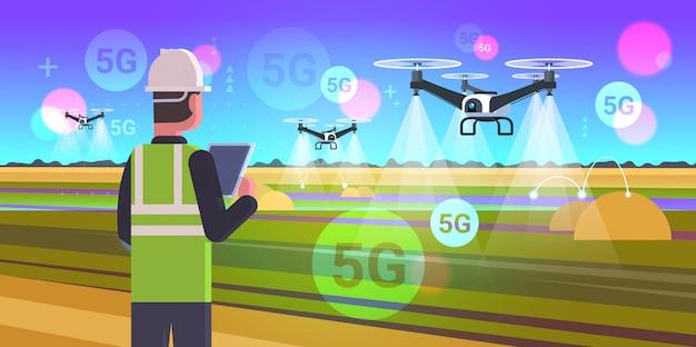 Boer met drone sprayer 5g online draadloze systeemverbinding vijfde innovatieve internetgeneratie slimme landbouwconcept landschap achtergrond vlak horizontaal portret